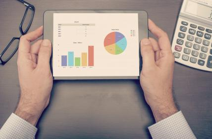 Businessman looking at statistics on tablet device